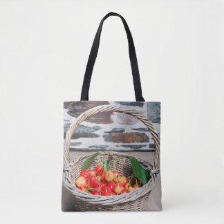 Cerises dans un panier sur un sac fourre-tout en
