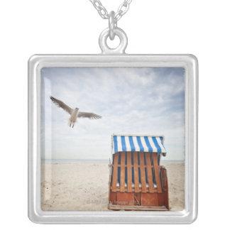 Chaise de plage en osier sur la plage pendentif carré