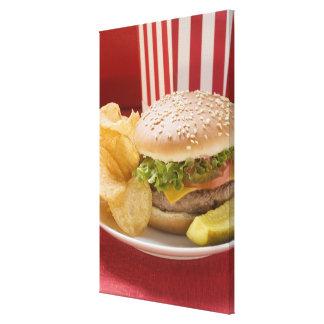 Cheeseburger avec les pommes chips et le cornichon toiles