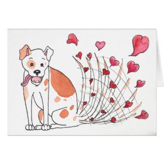 Chien heureux avec la carte de Valentine de coeurs