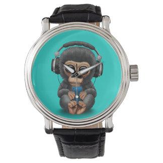 Chimpanzé de bébé avec les écouteurs et le montres bracelet