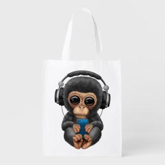 Chimpanzé de bébé avec les écouteurs et le sac d'épicerie