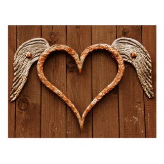 Coeur avec des ailes contre les conseils en bois carte postale