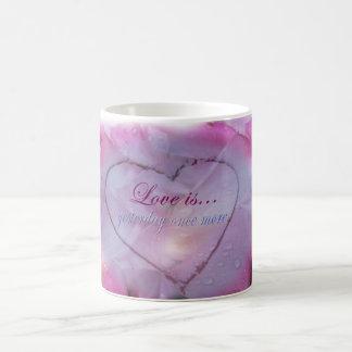 Coeur dans la tasse de neige et de pétales de rose