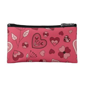 Coeurs et sac roses de cosmétique de fleurs