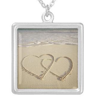 Collier Deux coeurs sus-jacents dessinés sur la plage avec