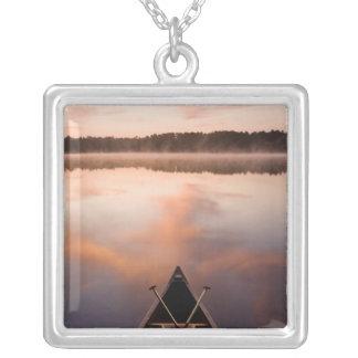 Collier Un canoë se repose sur le rivage du lac