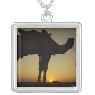 Collier un homme et son chameau silhouettés au coucher du