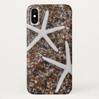 Coque iPhone X Squelettes d'étoiles de mer sur la plage en verre