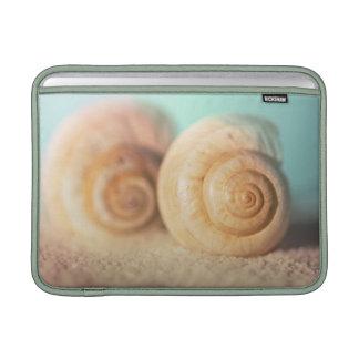 Coquilles de Nautilus sur la plage Poches Macbook