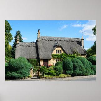 Cottage de toit couvert de chaume en ébréchant posters