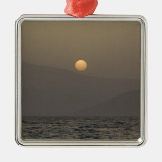 Coucher du soleil au-dessus des montagnes d'île de ornement carré argenté