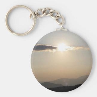 Coucher du soleil au-dessus des montagnes porte-clé rond