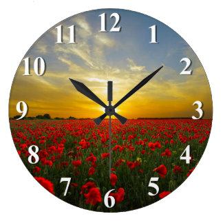 Coucher du soleil au-dessus d'un champ rouge de grande horloge ronde