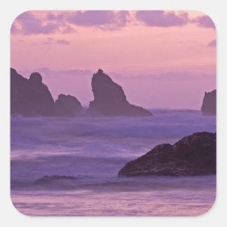 Coucher du soleil aux piles de mer de plage de sticker carré