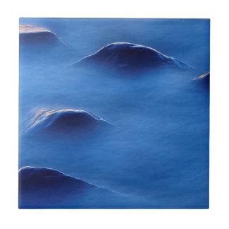 Coucher du soleil sur des roches dépassant par petit carreau carré