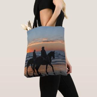Couples d'équitation sur la plage au sac