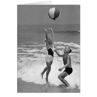 Couples jouant avec un Beachball Carte De Vœux