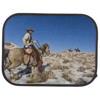 Cowboy avec des chevaux sur la gamme sur la tapis de sol