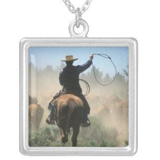 Cowboy sur le cheval avec le lasso conduisant des pendentif carré