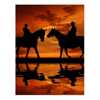 Cowboys d'équitation dans le coucher du soleil carte postale