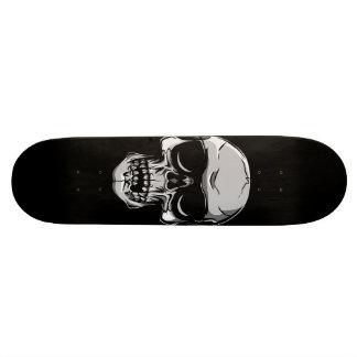 Crâne avec des lunettes de soleil sur la planche à plateaux de skateboards customisés