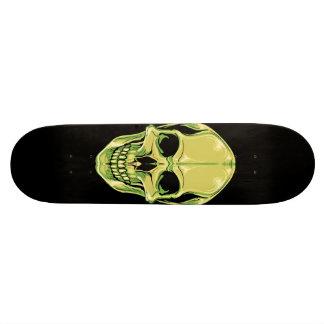 Crâne de grimacerie vert sur la planche à plateaux de planche à roulettes