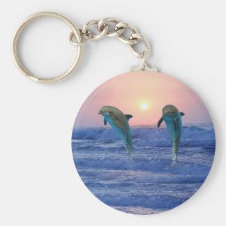 Dauphins au lever de soleil porte-clé rond