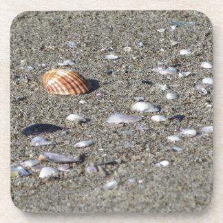 Dessous-de-verre Coquillages sur le sable. Arrière - plan de plage