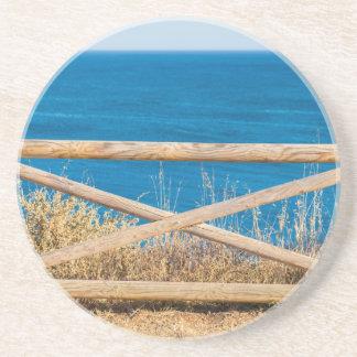 Dessous De Verre En Grès Barrière en bois à la côte avec sea.JPG bleu