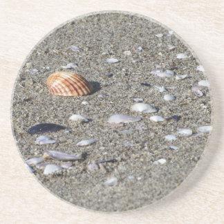 Dessous De Verre En Grès Coquillages sur le sable. Arrière - plan de plage
