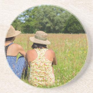 Dessous De Verre En Grès Deux amis s'asseyant ensemble dans meadow.JPG