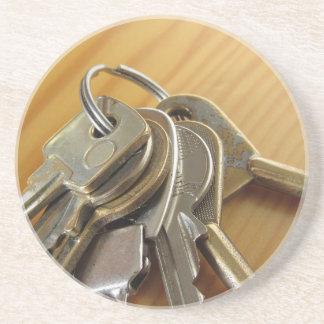 Dessous De Verre En Grès Groupe de clés usées de maison sur la table en