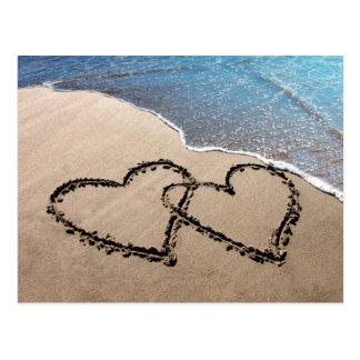 Deux coeurs dans la carte postale de plage de sabl