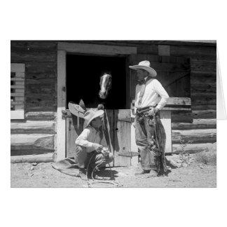Deux cowboys se tenant à côté d'une grange avec un carte de vœux