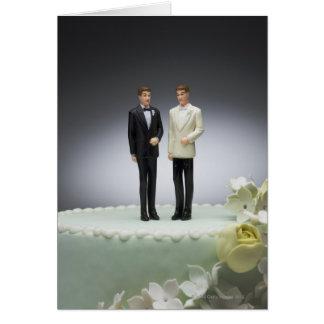 Deux figurines de marié sur le gâteau de mariage carte de vœux