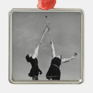 Deux joueurs de lacrosse sautent pour la boule ornement carré argenté