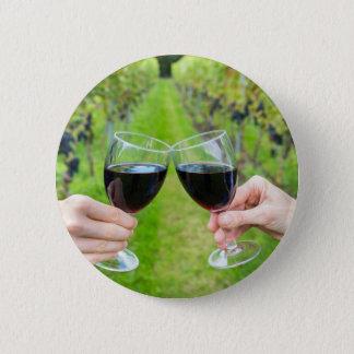 Deux mains grillant avec des verres de vin dans le badge