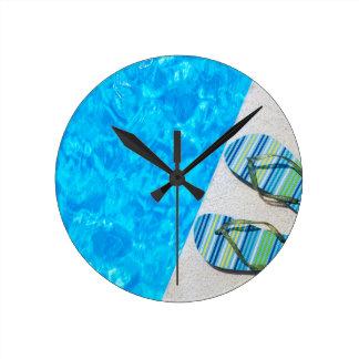 Deux pantoufles se baignantes sur le bord de la horloge ronde