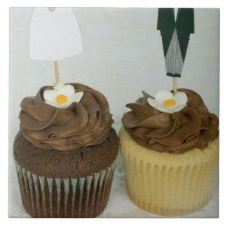 Deux petits gâteaux avec des jeunes mariés de grand carreau carré