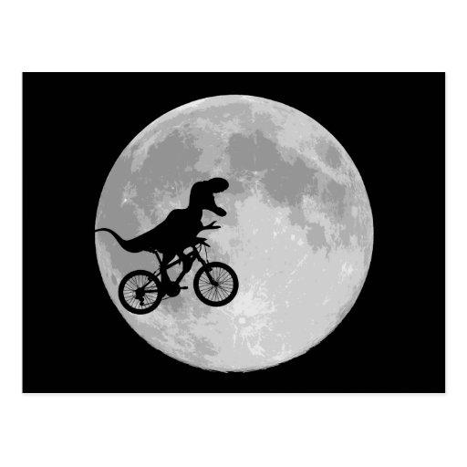 Dinosaure sur un vélo en ciel avec la lune carte postale