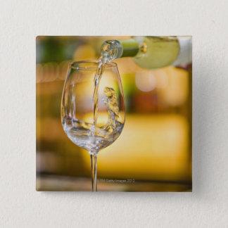 Du vin blanc est versé de la bouteille dans le badges