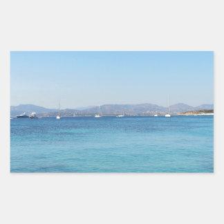 Eau et bateaux de mer clairs de turquoise sur sticker rectangulaire