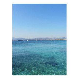 Eau et bateaux de mer clairs de turquoise sur carte postale