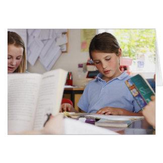 écolière se concentrant sur la lecture dans la carte de vœux