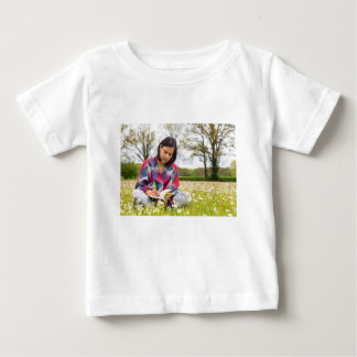 Écriture de femme dans le pré avec des fleurs de t-shirt pour bébé
