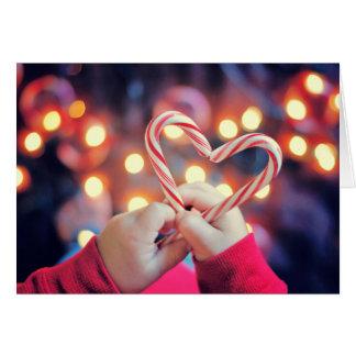 Enfant tenant la sucrerie de Noël avec la forme de Carte De Vœux
