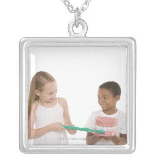 Enfants avec un ensemble modèle de dents et pendentif carré