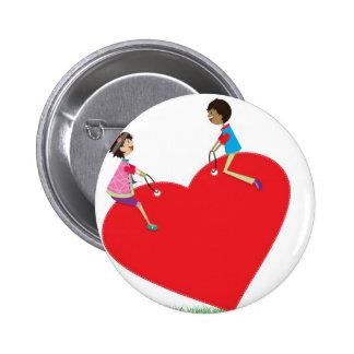 enfants jouant sur une bascule en forme de coeur pin's