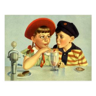 Enfants vintages, garçon et fille partageant une carte postale